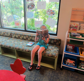 child reading book in library