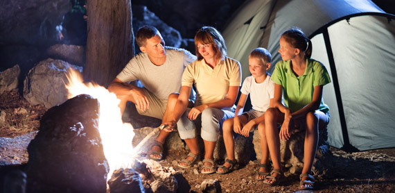 family camping next to campfire