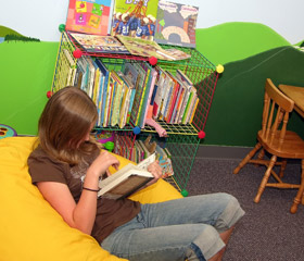middle school girl reading book in library