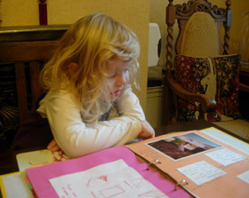 young girl viewing scrapbook pages
