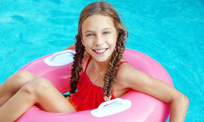 preteen braided girl on pink pool float