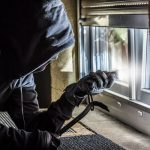 burglar shining flashlight through window opening