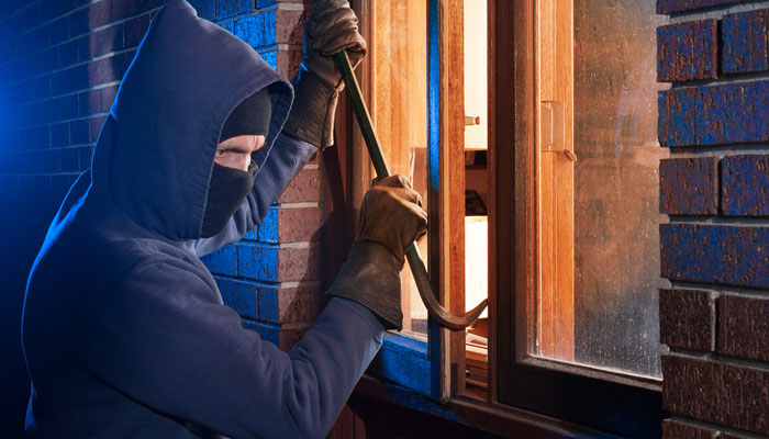burglar with crowbar forcing open double windows