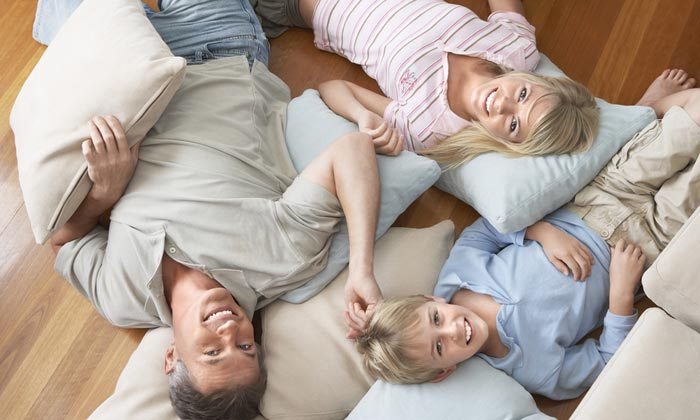 family sprawled on floor pillows