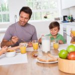 young family sitting at table eating