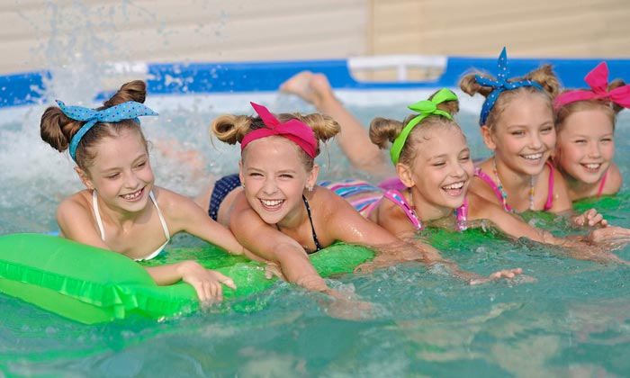 five young girls in swimming pool on floats