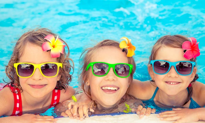 smiling young faces of sunglass girls in pool