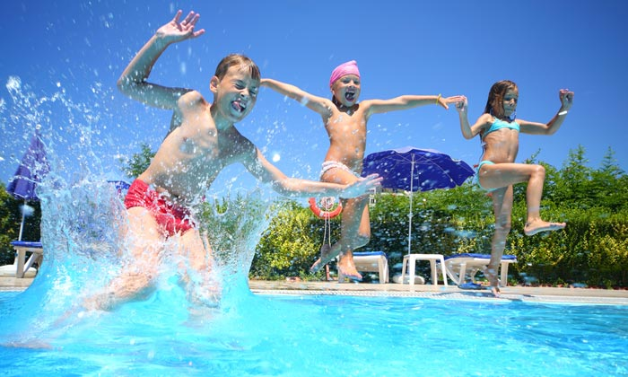 three kids jumping into swimming pool