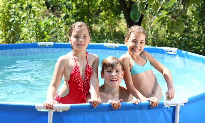 three kids standing inside swimming pool