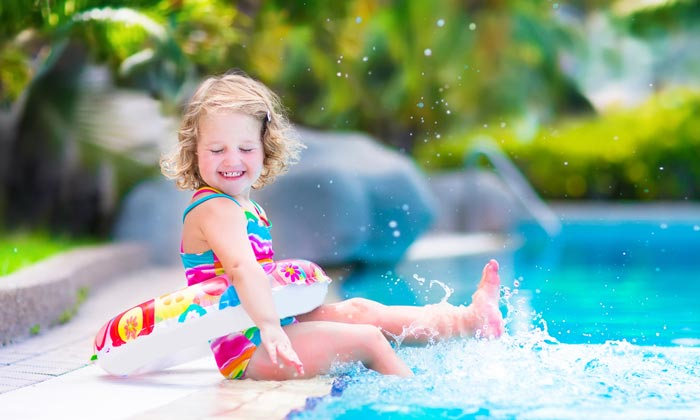 toddler girl with float by pool edge