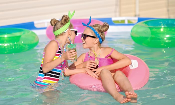 two young girls on floats in pool