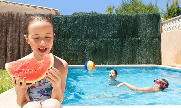 young girl biting watermelon by pool edge