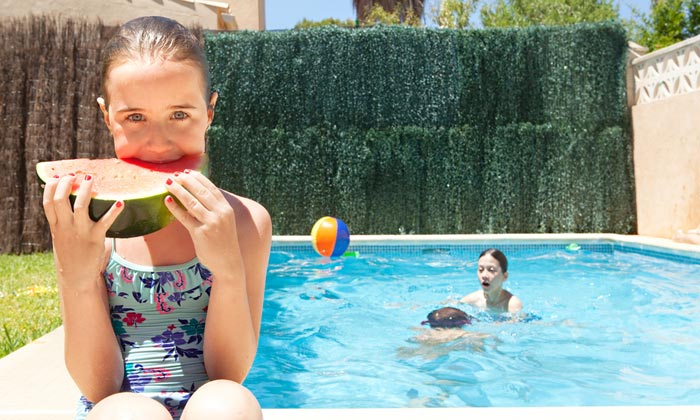 young girl eating watermelon by pool edge