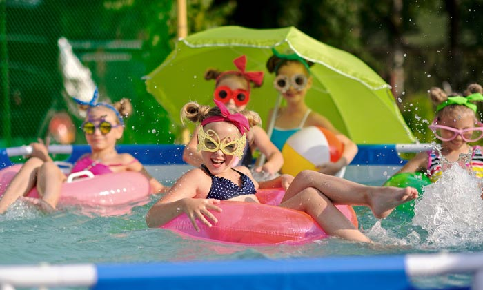 young girls in pool on floats with umbrellas