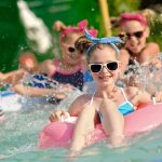 young girls on floats splashing in pool