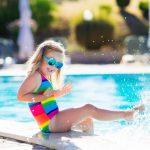 young toddler girl in rainbow swimming suit kicking