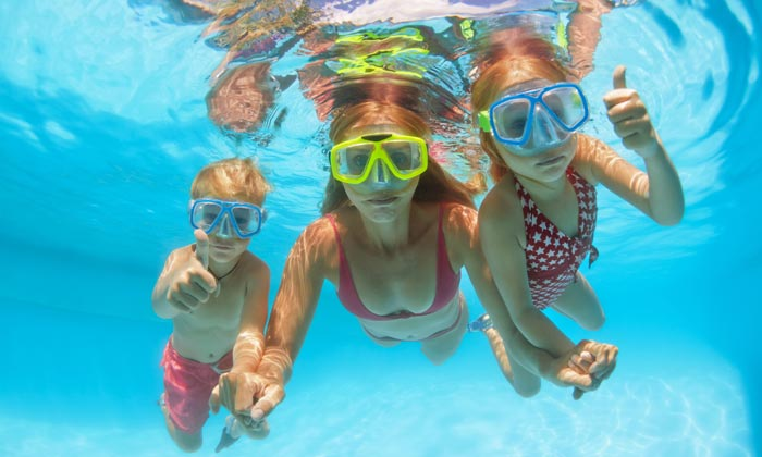 girl and brother with mother swimming underwater