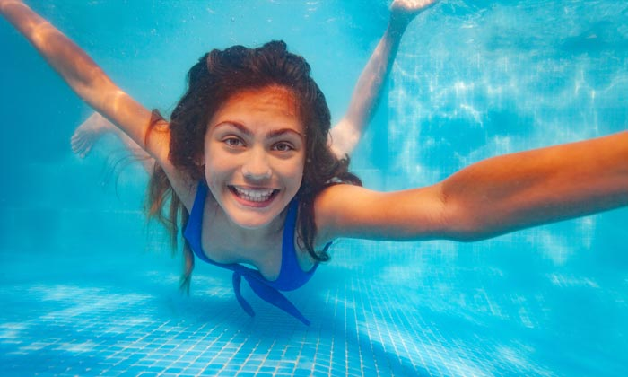 grinning swimming underwater girl