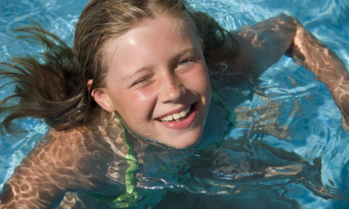 pretty girl smiling while in pool water