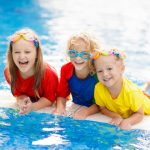 three happy kids leaning in swimming pool