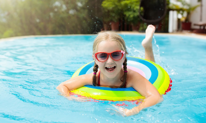 happy little girl floating on a pool tube