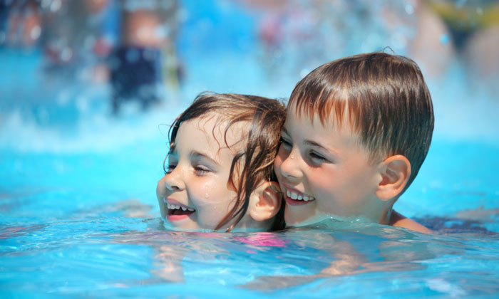 young brother and sister laughing in pool water