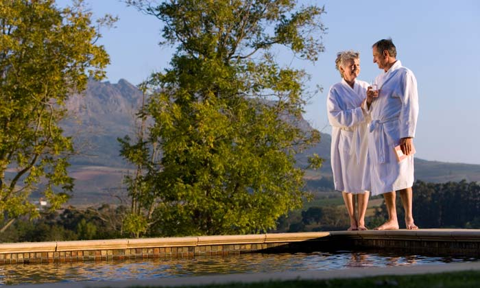 senior citizens in bathrobes standing by pool edge