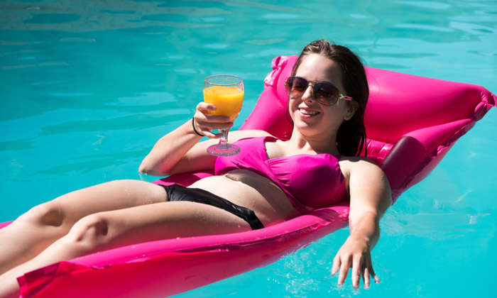 sunglasses woman floating drinking juice