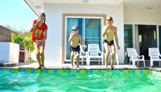 three kids jumping into backyard pool