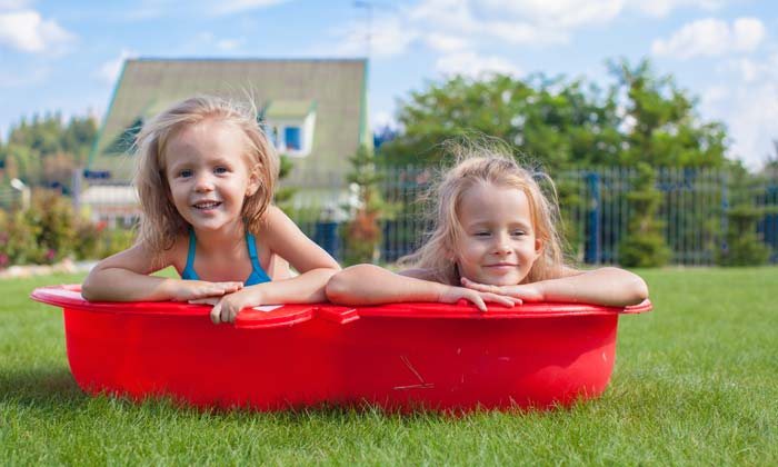 two little girls in red toddler wading pool