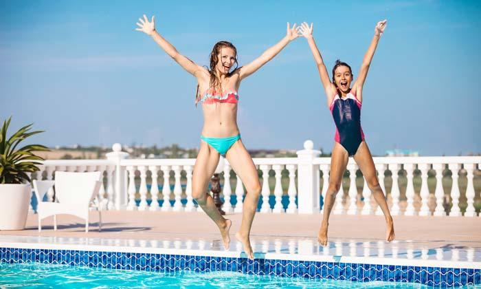 two teen girls jumping into inground pool