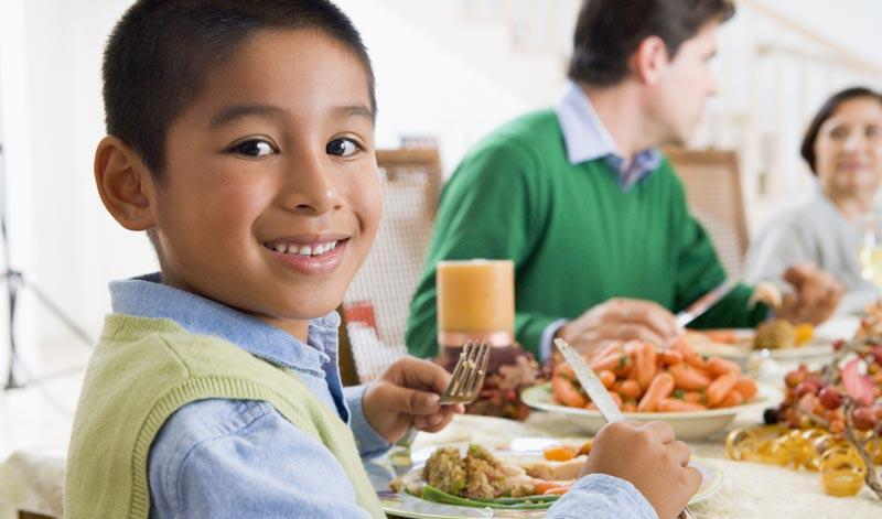 boy at dinner table enjoying food