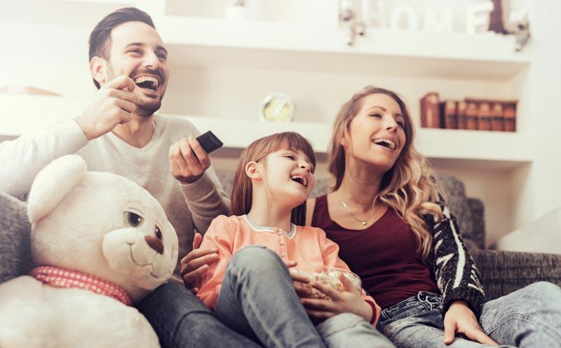 family movie time on sofa with teddy bear